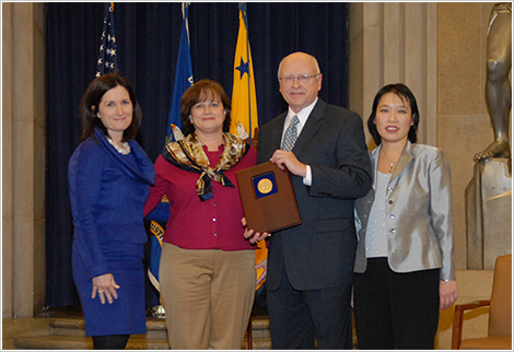 Assistant Attorney General Christine Varney presents a 2010 AAG Team Award to the Bank Merger Program Team. (L-R) Assistant Attorney General Christine Varney, Erin Carter Grace, Richard Gebert, and Angela Ting.