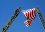 photograph of two fire truck ladders, one with an American flag