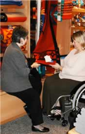 photograph of a woman in a wheelchair shopping with another woman