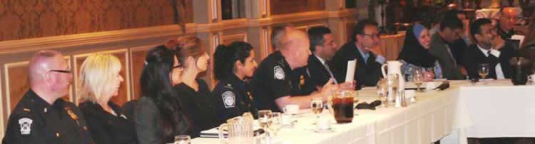 photograph of law enforcement officers with Arab and Muslim community members sitting together at a table