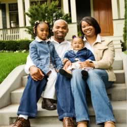 photograph of an African American family in front of a house