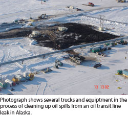 Photograph shows several trucks and equiptment in the process of cleaning up oil spills from an oil transit line leak in Alaska.