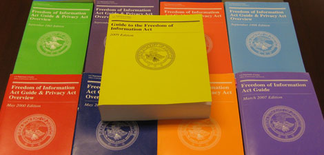 The 2009 Edition of the DOJ Guide to the Freedom of Information Act, surrounded by previous editions of the Guide.