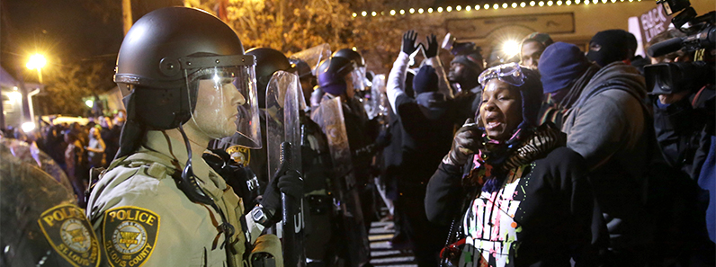 Police officers stand guard as protesters react in Ferguson, MO