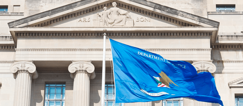 Blue Department of Justice flag waving in front of the main Department of Justice building.