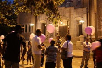 General public holding balloons in front of the church