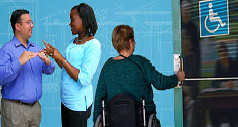 image showing two people using sign language and a woman using a wheelchair opening a door