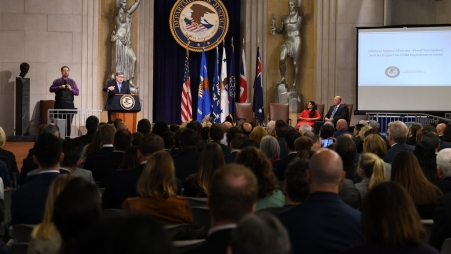 Attorney General William Barr speaking at a podium at the Lawful Access Summit