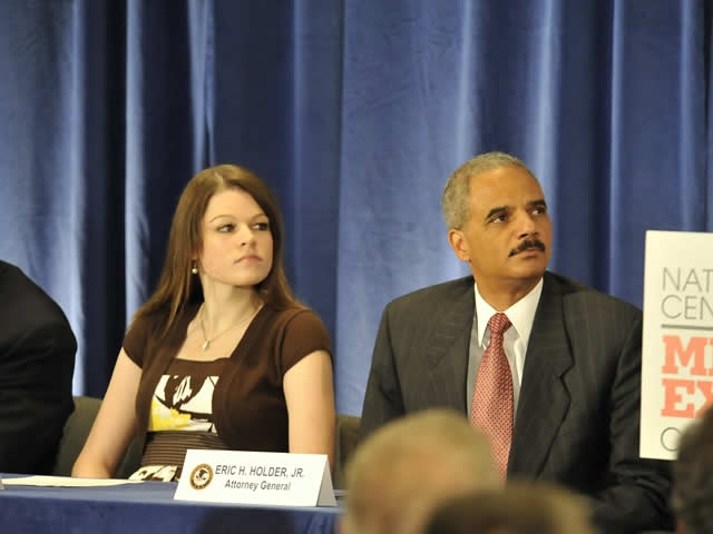 Melissa, who was on hand to share her personal story during the press conference, and Attorney General Holder, listen to one of the speakers.