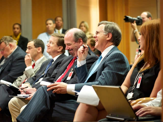 Members of the press react to an unexpectedly light moment during the press conference.