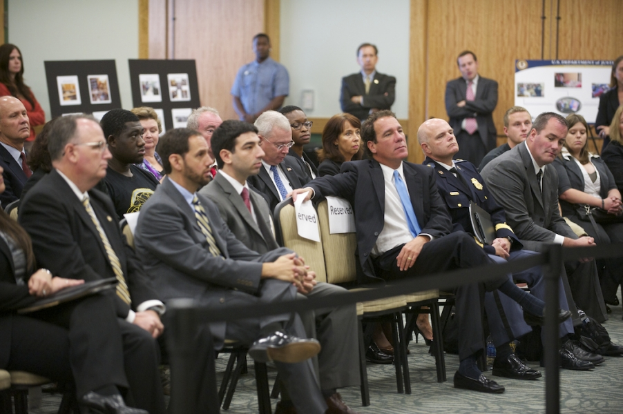 A crowd listens as AG Holder,  DAG Cole and US Attorney Rosentein discuss  efforts for the protection of intellectual property.