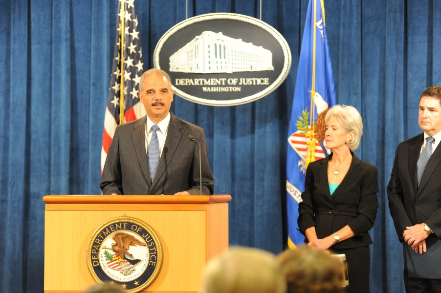 Attorney General Eric Holder delivers remarks while Health and Human Services Secretary Kathleen Sebelius and FBI Associate Deputy Director Kevin Perkins look on.