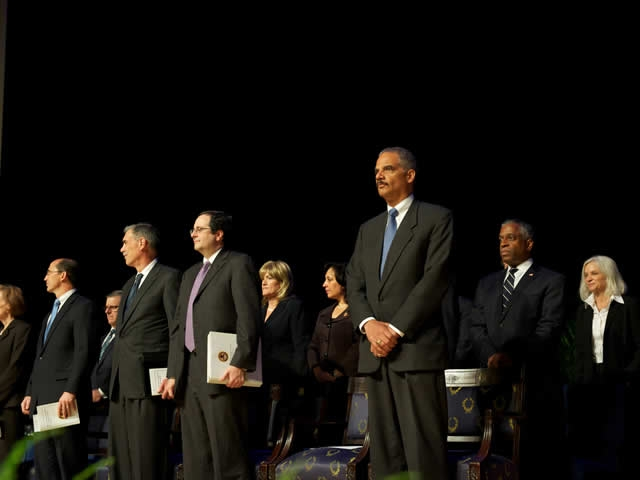 Attorney General Holder is accompanied on stage by leaders from across the Justice Department.