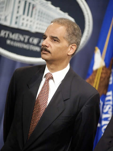 Attorney General Holder looks on.