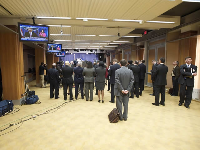 Members of the press and administration aides look on from the back of the press briefing room.