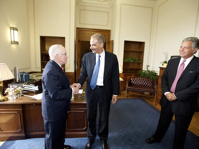 Attorney General Holder greets former Attorney General Mukasey.