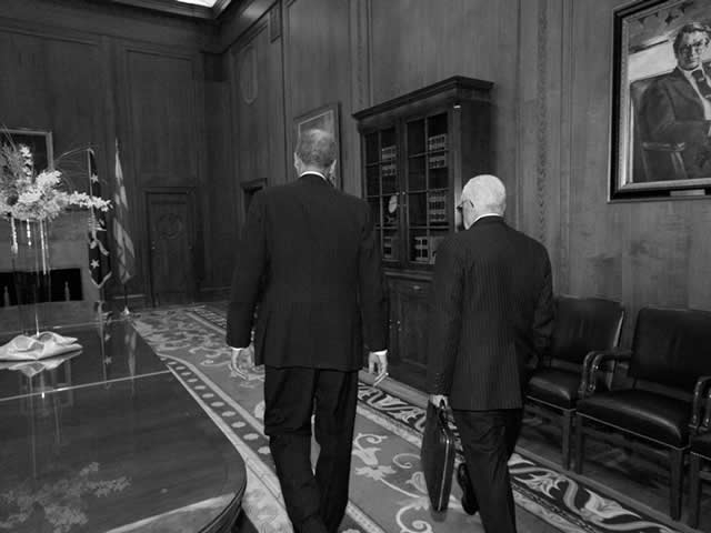 Attorney General Holder and former Attorney General Mukasey, walking.