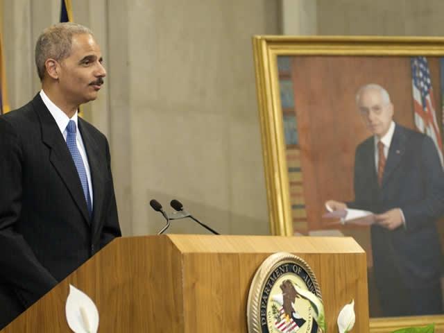 Attorney General Holder speaks next to the portrait.