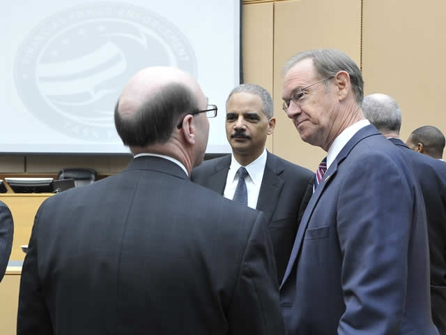 Attorney General Eric Holder and Arizona Attorney General Terry Goddard listen to a summit participant.