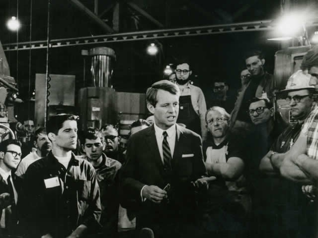 Attorney General Robert F. Kennedy talks with laborers.