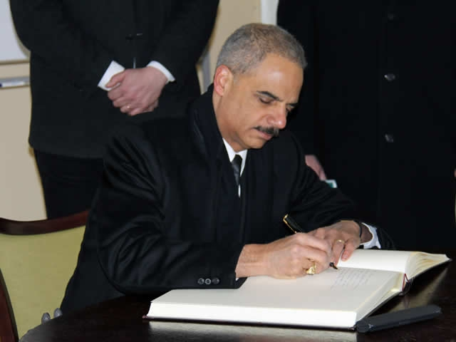 Attorney General Holder signs the guest book at the Auschwitz-Birkenau Memorial and State Museum.