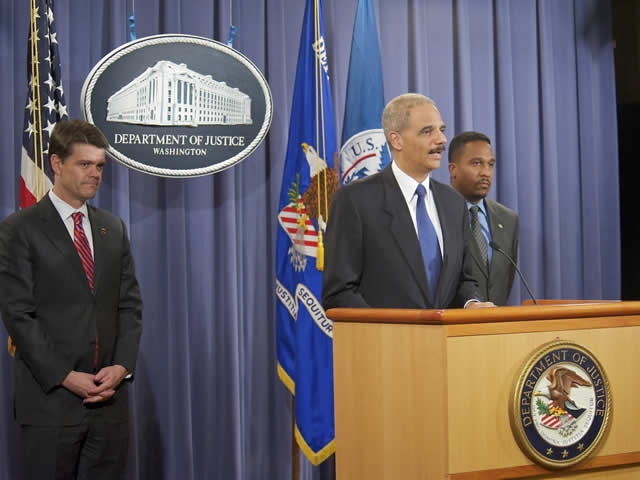 Attorney General Holder at the podium and flanked by John Morton, Director of Immigration and Customs Enforcement and Ron Machen, United States Attorney for the District of Columbia.