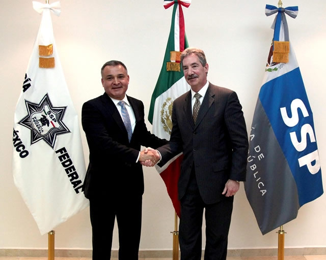 Deputy Attorney General James Cole and Mexican Secretary of Public Security Genaro Garcia Luna standing shaking hands