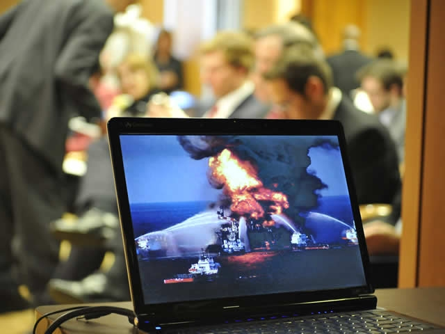 A view of the press conference audience behind a computer image of the fire on the Deepwater Horizon oil platform.