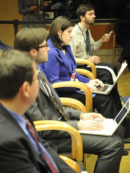 Press conference attendees study the briefing materials and listen to the presenters.
