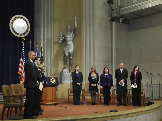 Department executives and panel members stand for the opening of the Stalking Awareness Event.