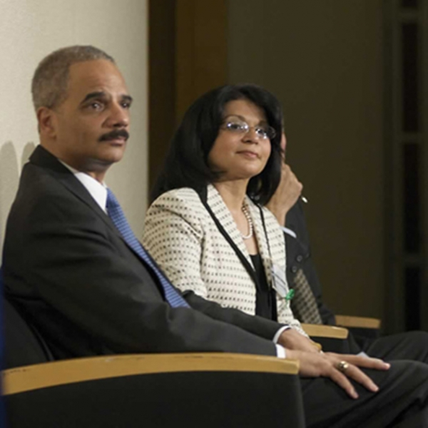 Attorney General Holder sitting next to Assistant Attorney General Moreno at the ceremony