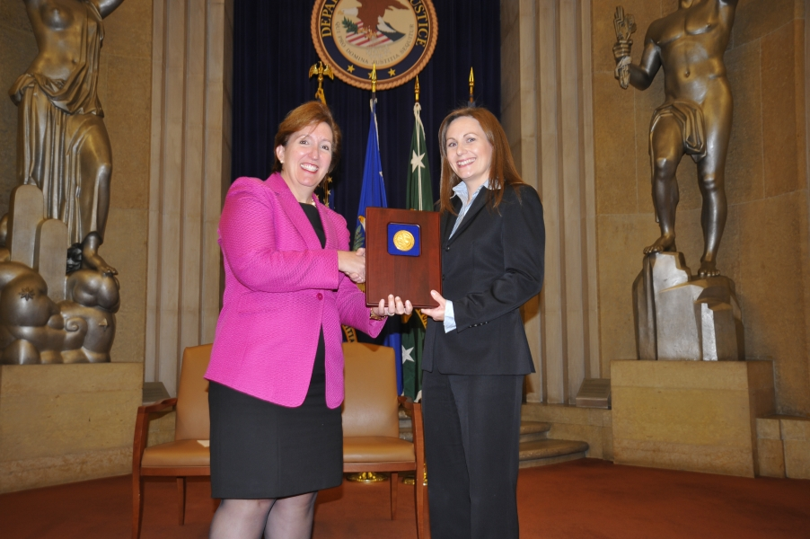Acting Assistant Attorney General Sharis Pozen presents a 2011 Assistant Attorney General Award to Christine Hill.