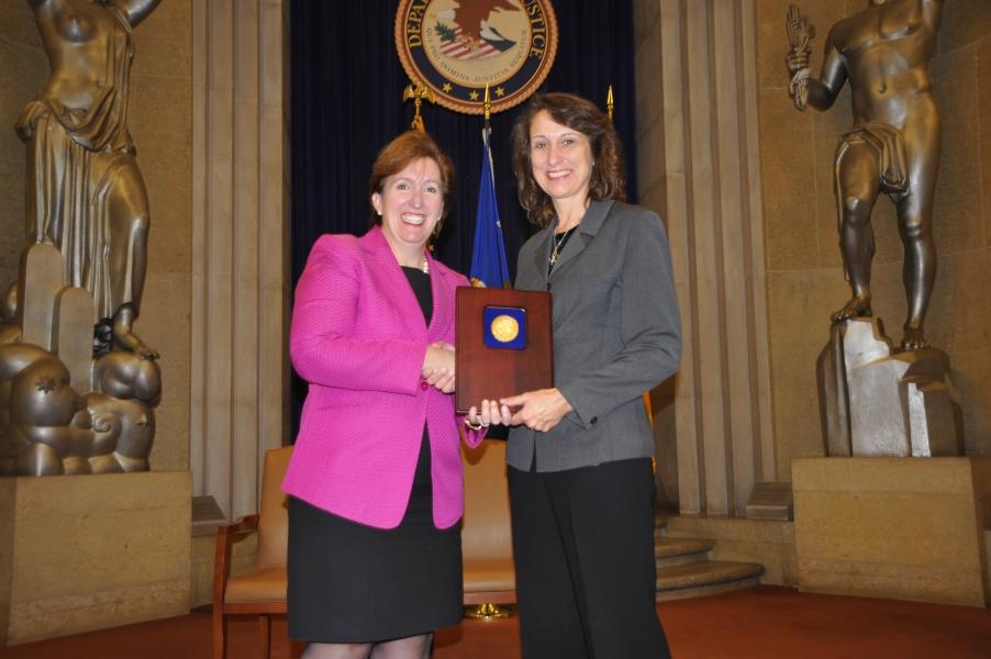 Acting Assistant Attorney General Sharis Pozen presents a 2011 Assistant Attorney General Award to Janet Ficco.