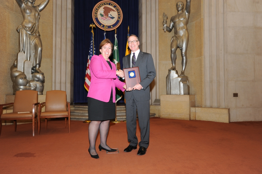 Acting Assistant Attorney General Sharis Pozen presents the 2011 Roberts Award to Jim Tierney.