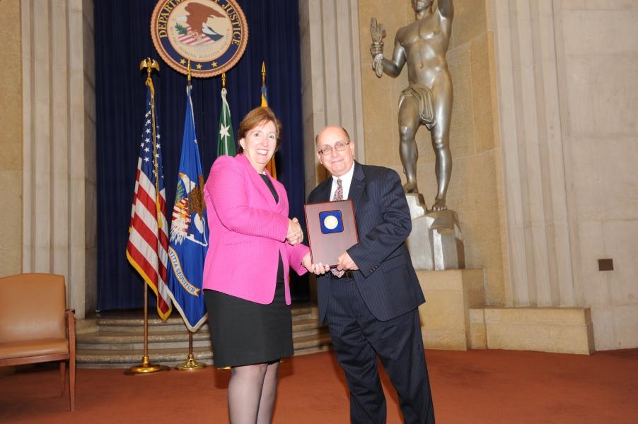 Acting Assistant Attorney General Sharis Pozen presents the 2011 Enforcement Support Award to Joseph Sutton.