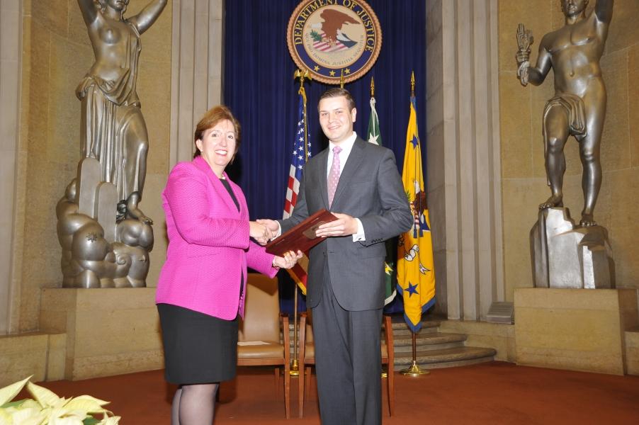 Acting Assistant Attorney General Sharis Pozen presents a 2011 Assistant Attorney General Award to Roman Babadzhanov.
