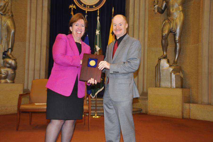 Acting Assistant Attorney General Sharis Pozen presents a 2011 Assistant Attorney General Award to Wayne Dunham.