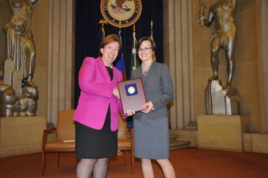 Acting Assistant Attorney General Sharis Pozen presents a 2011 Assistant Attorney General Award to Yvette Tarlov.