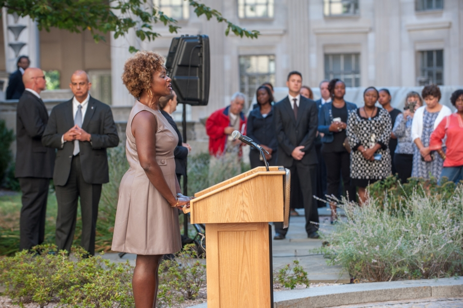 Rhea Walker, Special Assistant, Office of Justice Programs, sings God Bless America during the commemoration ceremony of the 14t