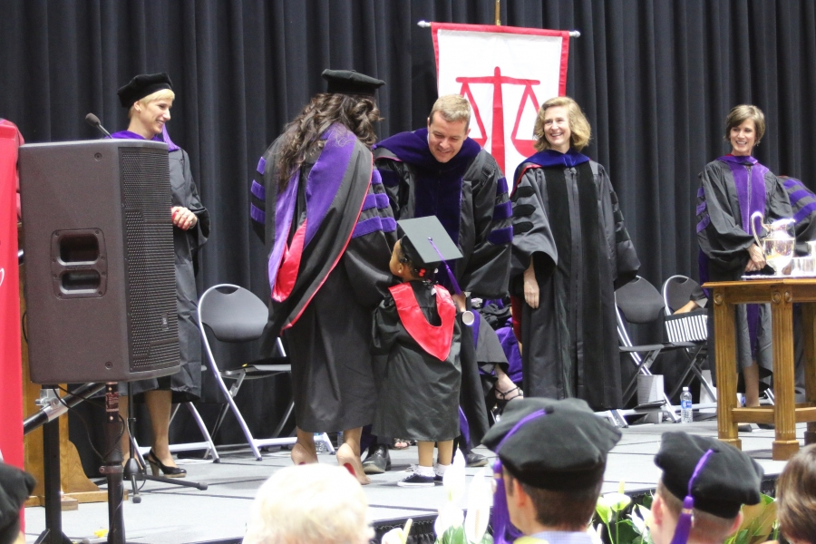 Graduate and daughter in cap and gown at the University of Georgia School of Law.