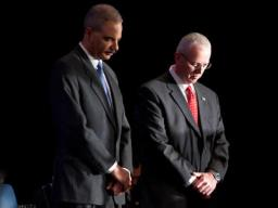 Attorney General Holder and Director Clark showing respect during the invocation.