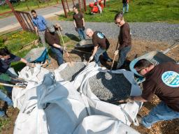 ENRD volunteers shoveling gravel into wheelbarrows