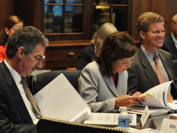 Deputy Attorney General James Cole and Secretary of Labor Hilda Solis along with Shawn Donovan, Housing and Urban Development Secretary, look over the meeting details