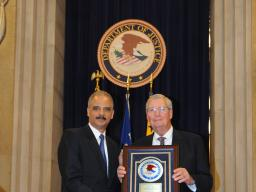 Attorney General Eric Holder honors former Assistant Attorney General James F. Rill with the 2012 Sherman Award.