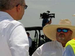 The Attorney General pauses to hear the perspective of a worker involved in cleaning the beach.
