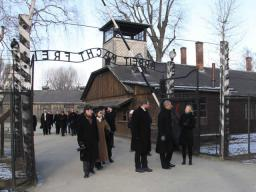 Attorney General Holder, accompanied by the Auschwitz-Birkenau Memorial and State Museum Director Piotr Cywinski, walk under the infamous entrance to the Auschwitz I concentration camp.