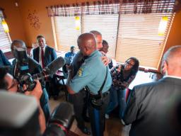 Attorney General Eric Holder hugs Missouri Highway Patrol Captain Ron Johnson at Drake's Place restaurant.