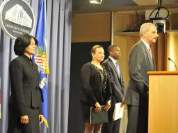 Attorney General Eric Holder at the podium. Behind him are from left to right: Assistant Attorney General Ignacia Moreno, who leads DOJ's Environment and Natural Resources Division;  Environmental Protection Agency Administrator Lisa Jackson;  and Assistant Attorney General Tony West, head of the Justice Department's Civil Division.