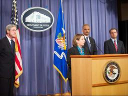 FBI Director Robert Mueller, Attorney General Eric Holder, and U.S. Attorney for the Southern District of New York Prett Bharara look on to Assistant Attorney General for National Security Lisa Monaco, as she recognizes the efforts of the multiple agencies and offices that participated in the investigation.