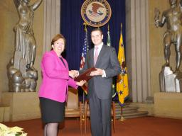 Acting Assistant Attorney General Sharis Pozen presents a 2011 Assistant Attorney General Award to Roman Babadzhanov.
